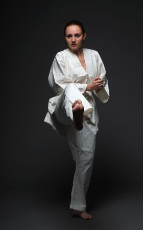 Youth woman throws forward right leg in the dark background. She is wearing white uniform of Asian martial art. She is barefooted. Her long hair are combed out smoothly. Sportswoman is concentrated and self-disciplined. photo