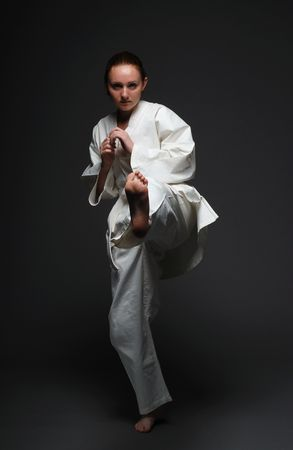Youth woman throws forward left leg in the dark background. She is wearing white uniform of Asian martial art. She is barefooted. Her long hair are combed out smoothly. Sportswoman is concentrated and self-disciplined. photo