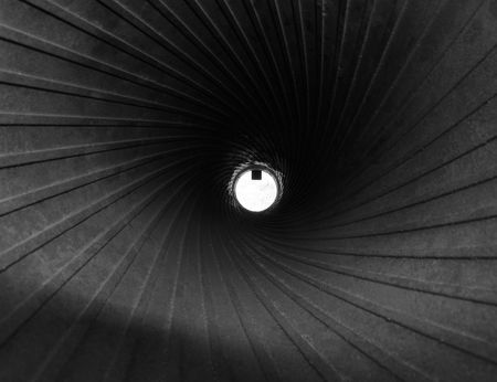 backsight: White disk with shiny steel spirals of rifling, view of cannon barrel on the inside, monochrome image