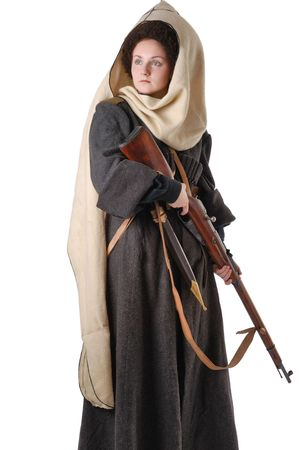 cossack: Unfriendly girl is holding rifle isolated on white. She is wearing vintage uniform of Russian foot Cossack in time First World War. She is dressed in woolen greatcoat, fur-cap and white hood. She is carried a dagger.