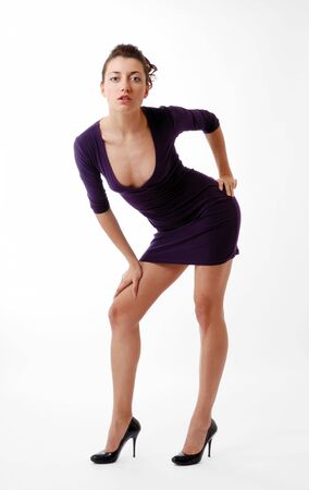 Pretty brunette bending forward isolated on white. Other hand is leant on a knee, another on a hip. She is wearing short slinky dress with low decollete and black pumps with high heels. photo