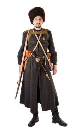vintage military rifle: Young man is wearing vintage uniform of Russian foot Cossack in time First World War. He is dressed in woolen greatcoat, fur-cap and boots. He is carried military equipment. He has a dagger and a rifle.