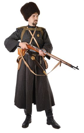 vintage military rifle: Young man is wearing vintage uniform of Russian foot Cossack in time First World War. He is holding rifle. He is dressed in woolen greatcoat, fur-cap and boots. He is carried military equipment.