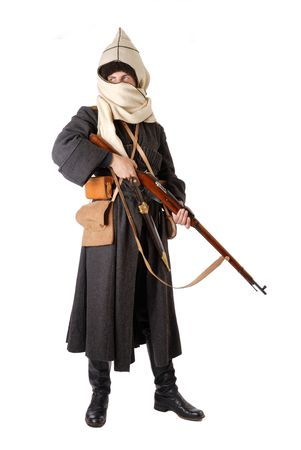 Young man is wearing vintage uniform of Russian foot Cossack in time First World War. He is holding rifle. He is dressed in woolen greatcoat, fur-cap and boots. His face is closed with hood. He is carried military equipment.