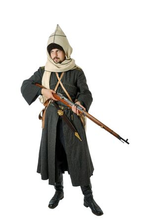 vintage military rifle: Young man is wearing vintage uniform of Russian foot Cossack in time First World War. He is holding rifle. He is dressed in woolen greatcoat, fur-cap, hood and boots. He is carried military equipment.