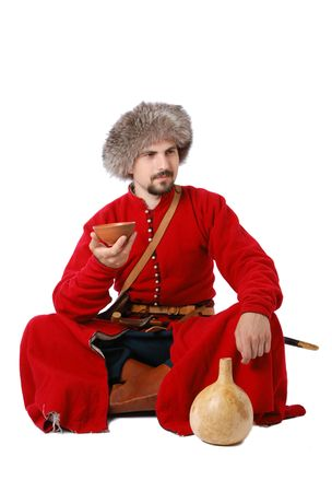 17th century: Young man is wearing vintage uniform of Tatar foot warrior of 17th century. He is sitting and holding a cup. He is dressed in red caftan, fur-cap. He is carried military equipment.