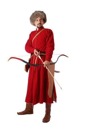 17th: Young man is wearing vintage uniform of Tatar foot warrior of 17th century. He is holding a bow with an arrow. He is dressed in red caftan, fur-cap and boots. He is carried a quiver and a saber.