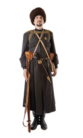 vintage military rifle: Young man is wearing vintage uniform of Russian foot Cossack in time First World War. Russian Cossack is standing still. He is dressed in woolen greatcoat, fur cap and boots. He is carried military equipment. He has a dagger and a rifle.