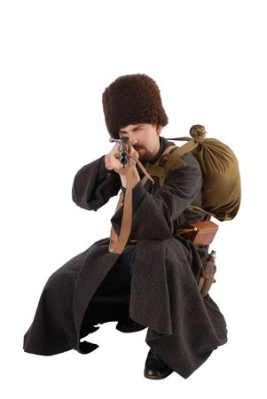greatcoat: Young man is wearing vintage uniform of Russian foot Cossack in time First World War. Russian Cossak is squatting and aiming a rifle at camera. He is dressed in woolen greatcoat, fur cap and boots. He is carried military equipment.  Stock Photo