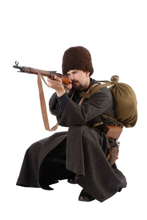 Young man is wearing vintage uniform of Russian foot Cossack in time First World War. Russian Cossak is squatting and aiming a rifle. He is dressed in woolen greatcoat, fur cap and boots. He is carried military equipment.  photo