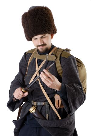 greatcoat: Young man is wearing vintage uniform of Russian foot Cossack in time First World War. Russian Cossak is looking over a dagger. He is dressed in woolen greatcoat, fur cap and boots. He is carried military equipment.  Stock Photo