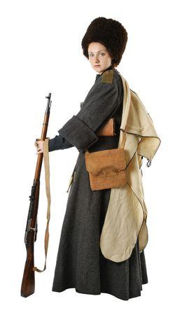 reenactor: Joven es llevar uniforme cosecha de pie ruso cosacos en tiempo de guerra. Ella es miembro de la recreaci�n hist�rica. Cosacos rusos est� de pie. Re-enactor est� vestido de lana greatcoat, la tapa de pieles y el cap�. Ella tiene bolsas y un fusil.