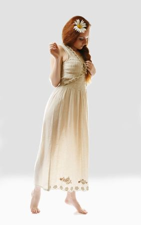 Young woman is standing on tiptoe and looking down. She is wearing long linen dress. Her maidenly body is illuminated from beneath. She is barefooted and isolated on white. Big camomile is decorated luxuriant red hair. photo