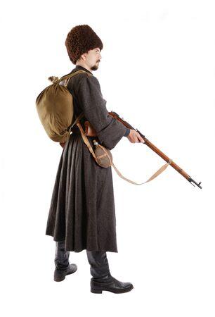 reenactor: Joven es llevar uniforme cosecha de pie ruso cosacos en tiempo de guerra. Es miembro de la recreaci�n hist�rica. Cosacos rusos est� de pie con un rifle. Re-enactor est� vestido de lana greatcoat, tapa de pieles y botas. �l tiene una mochila y una f