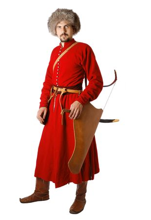 17th century: Young man is wearing vintage uniform of Tatar warrior of 17th century. Bearded re-enactor is armed with a saber and a bow. He is dressed in red caftan, fur cap. He is member of Society of Historical Reenactment.