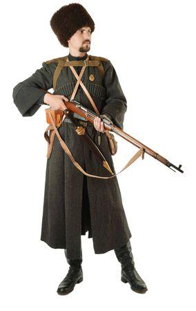 reenactor: Joven es llevar uniforme cosecha de pie ruso cosacos en tiempo de guerra. Es miembro de la recreaci�n hist�rica. Cosacos rusos est� de pie con un rifle. Re-enactor est� vestido de lana greatcoat, tapa de pieles y botas.