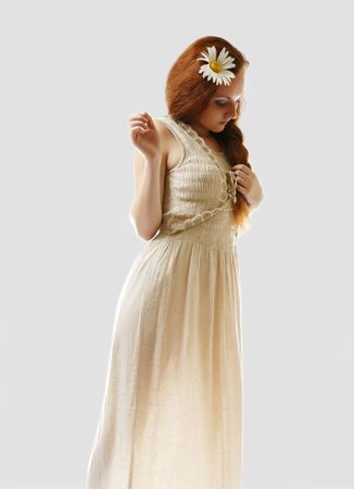 Young woman is standing sideways and looking down. She is wearing long linen dress. Her maidenly body is illuminated from beneath. She is isolated on white. Big camomile is decorated luxuriant red hair. photo
