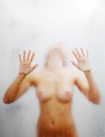 Nude girl is putting her palms on weeping glass of shower bath. She is bending backwards. Her blurred silhouette is visible through sweat glass surface with water drops and streams. Focus is on the wet glass wall of shower cabin. photo
