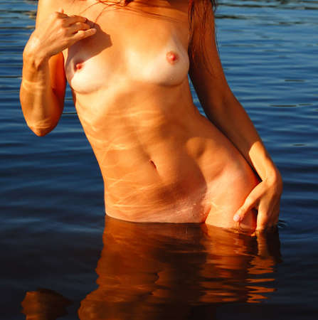 nude woman standing: There is a part of female body with many patches of sunlight. A nude woman are bathing in sunshine and quiet water.  Stock Photo