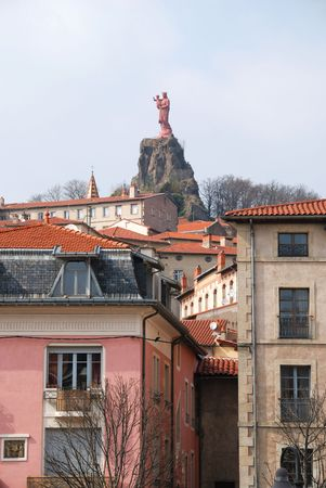 There is a residential district of an old world city. The sculpture of Madonna and Child is towering over the town. photo