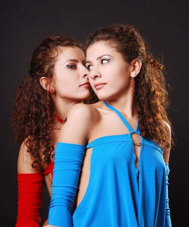 Two young women are whispering. The attractive gemini talk privately between them. Pretty twins are wearing the same cocktail dresses with different colours. Stock Photo - 6629697