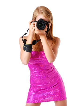 legs apart: An attractive girl is shooting with DSLR. She is wearing a rosy strapless dress. She is standing with her legs apart. Her sexy body is beautifully accentuated with the shining dress outlines the figure. Stock Photo