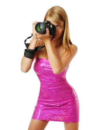 An attractive girl is shooting with DSLR. She is wearing a rosy strapless dress. She is standing with her legs apart. Her sexy body is beautifully accentuated with the shining dress outlines the figure. Standard-Bild