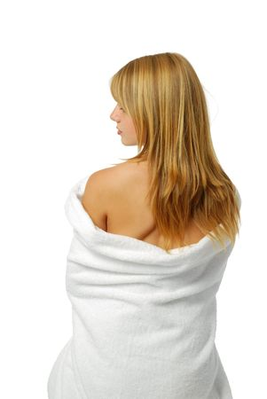 A blonde wrapped herself warm in a bath towel. She was photographed from back. The white towel slipped down and uncovered her back. The woman turned left her face. Her back was closed with fair hair.