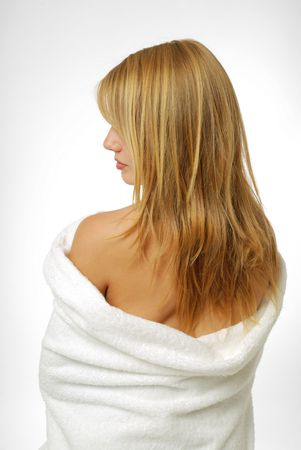 slipped: A blonde wrapped herself warm in a bath towel. She was photographed from back. The white towel slipped down and uncovered her back. The woman turned left her face. The face was closed with fair hair. Stock Photo