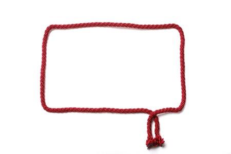 赤いフレームは編むことのためのコードで行われます。空であり、白で隔離されました。 写真素材