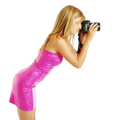 slinky: An attractive girl is bending forward and photographing with DSLR. She is wearing a pink strapless dress. The blonde is photographed from one side. Her sexy body is beautifully accentuated with the slinky dress.
