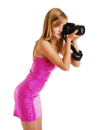 strapless dress: Pretty girl is photographing with a big camera. She is wearing a pink strapless dress. The blonde is photographed from one side. Her sexy body is beautifully accentuated with the slinky dress. Stock Photo