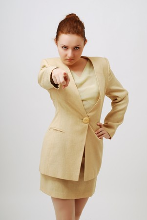 Serious young woman is pointing the index finger and looking at camera against a grey background. She is wearing a business suit. Her red hair is done smoothly. photo
