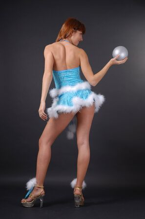 Young woman is stranding back. Pin-up is holding a silver christmas ball in outstretched arm on the dark background. She is wearing blue sexy suit decorated with white fluff.  photo