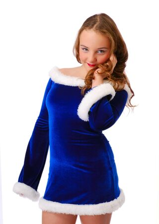loose hair: Shy teenage girl is tidying loose hair and looking at the camera. She is wearing blue velvety dress decorated with white fluff.   Stock Photo