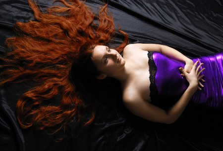 Young woman is lying on the black silk. Her long red hair is spread around head. Stock Photo - 7878256