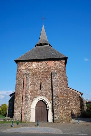 gascony: Very old stone church against the blue sky.