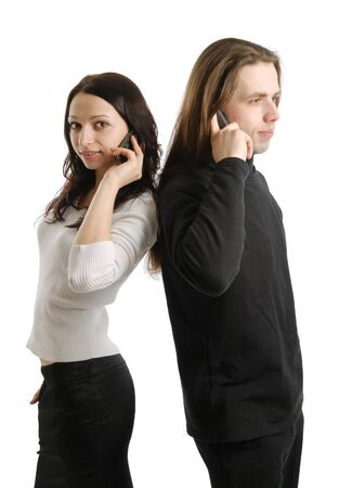 Young man and woman are standing back to back. They are calling by mobile phone at the same time. Happy girl is looking at the camera. photo