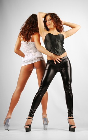 Two go-go are dancing back to back. Her legs is planted apart on high stiletto heels. The young women are twins. One of them is wearing black leather leggings and top. The other sister is wearing a white transparent dress.  Stock Photo - 7878262