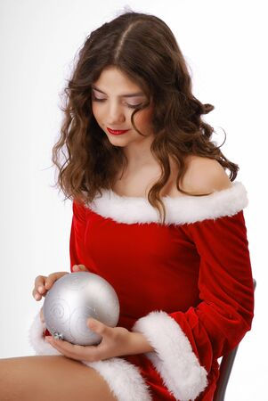 velvet dress: Sad teenage girl is dropping her eyes on the silver christmas ball. She is wearing red velvety dress decorated with white fluff.