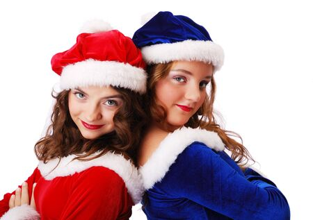 velvety: Happy teenage girls are clinging close to one another back to back. She are looking at the camera and smiling. She are wearing red and blue velvety dresses and caps decorated with white fluff.