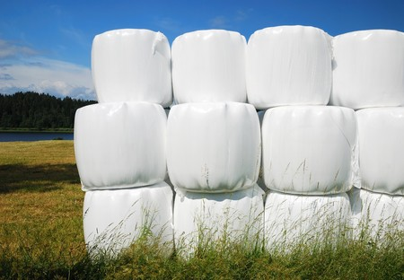 Swedish rural landscape with straw packages on the harvested field. In the foreground there is a stack of bales wrapped with white plastic film. photo