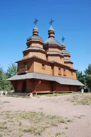 trampled: Village wooden church on the trampled hill above the blue sky.