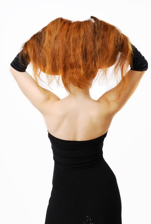 Red-haired woman is standing back with raised hair. She has lifted up her long red hair with both hands. She is wearing a strapless dress and long gloves. Her black clothes are accenting nude back and shoulders. photo
