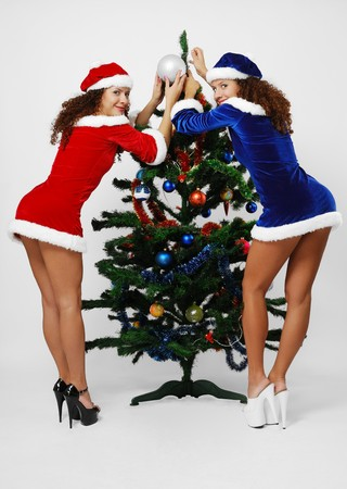 Two happy women are decorating the Christmas tree. Sexy twins are Santa Clauses. They are wearing velvety dresses and caps decorated with white fluff. photo