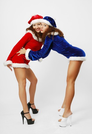 sisters sexy: Two happy women are greeting one another. Sexy twins are Santa Claus. They are wearing velvety dresses and caps decorated with white fluff. Stock Photo