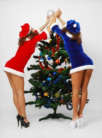 reaching out: Two happy women are decorating the Christmas tree. They are reaching out the top of fir-tree. Sexy twins are Santa Clauses. They are wearing velvety dresses and caps decorated with white fluff.