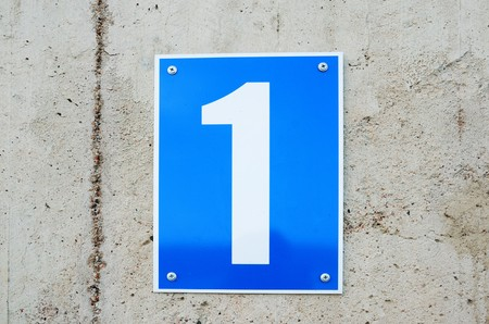 arabic numeral: Rectangular new blue sign hangs on the concrete wall. There is white figure of one on its.