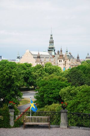 Cosy nook in the old green park with Swedish flag and bench. In the background there are ancient buildings of Stockholm. Stock Photo - 8260777