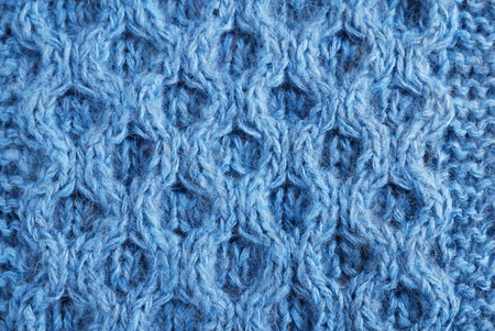 Blue knitted cloth is made by hand. It is decorated with vegetable bulging pattern. photo